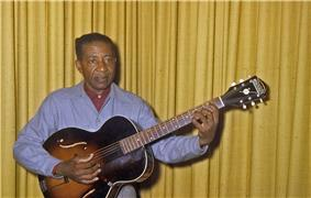 Lonnie Johnson posing with his guitar