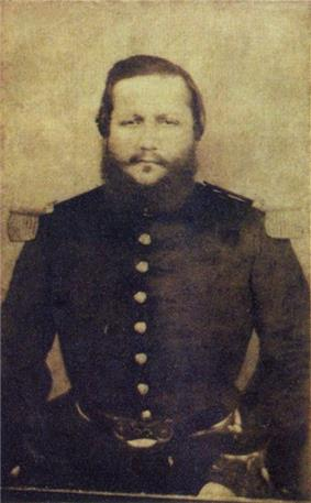 Head and torso of a large bearded man wearing military clothing.