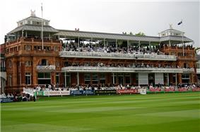 A brown coloured pavilion in front of a green field, surrounded by a number of banners