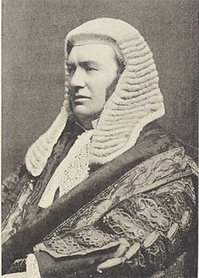 A man sitting relaxed and facing the right. He is in full judicial dress, with a wig, suit and heavy robe.