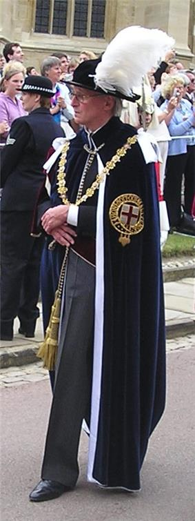 An elderly gentleman walking along. He is wearing a suit with grey trousers, over which is draped a heavy robe and a gold change. A black hat with a large white plume sits on his head. In the background stands a police woman separated from a group of people by a white cordon.