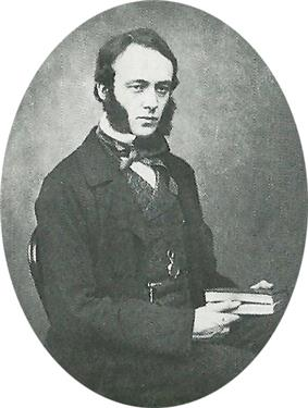 A young man with dark hair and huge sideburns