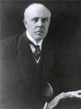 A balding, white-haired man wearing 1920s formal business attire (jacket and waistcoat with wing collar and tie) leans to his left on a table and looks directly at the viewer. His right hand rests in front of his left on the edge of the table next to some papers and a pen.