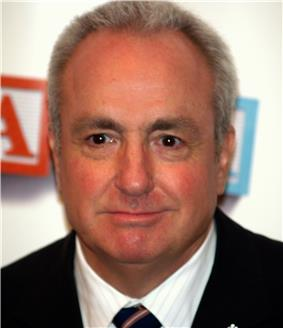 A close-up of Lorne Michaels—a middle-aged Caucasian man with white hair wearing a black suit—as he smiles