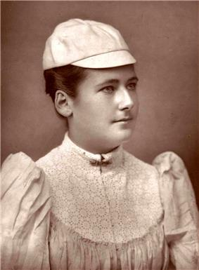 A black and white picture, a woman is in all-white attire with a hat on, and is looking sideways to the camera