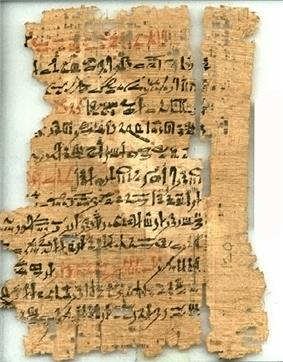 An ancient, torn and fragmented papyrus document, with cursive hieratic handwriting in black and red ink on its surface