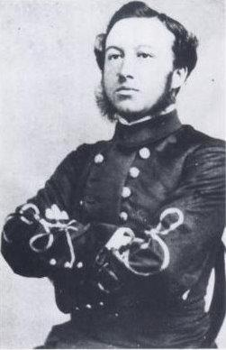 photograph of a man sitting upright, wearing a grey dress uniform
