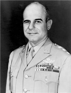 Head and shoulders of a balding middle-aged white man wearing a light-colored military jacket with three stars on the shoulder and four rows of ribbon bars and a winged pin on the left breast.