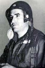 Head and shoulders of a white man wearing a metal helmet with an oak leaf emblem on the front, the chin strap unbuckled and hanging loose, and a dark, heavy coat.