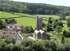 Looking down on the village with houses and stone church building with square tower.