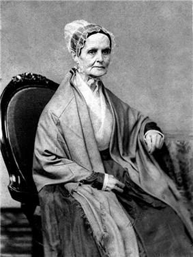 A monochrome photograph portrait of an elderly woman seated in a chair, wearing a heavy shawl over a white blouse, a simple lace bonnet covering hair held up on the back of the head, the woman turned somewhat to the right