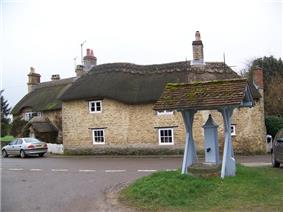 Cast iron pump with its own tiled roof. Behind are two stone built thatched cottages.