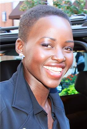 An African American female with a black automobile behind her is seen smiling. She is wearing a black coat.