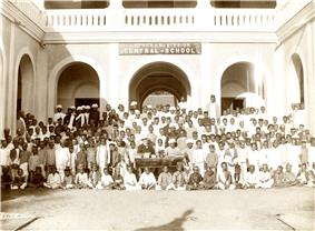 A group of students seated with a building in the background.