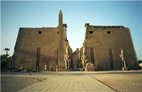 Pair of trapezoidal stone towers flanking a passage, beyond which a row of columns is visible. In front of the towers are several large statues and an obelisk.