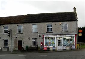 Small shop with white surrounds to the windows set in the right hand building of a terrace.