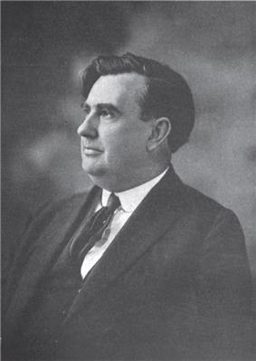 A portly man with wavy, black hair and a prominent nose, wearing a black jacket and tie and white shirt