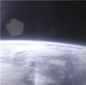 The edge of Earth, heavily overexposed, in the lower half of the image, with black space above. In between them, a blue haze layer from the atmosphere. There is a lens flare in one corner.