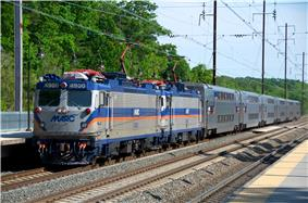 A large commuter train with blue and orange stripes sits at a train station.