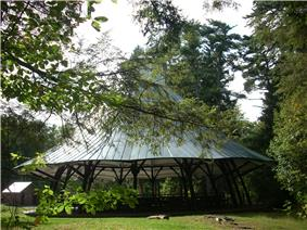 A conical green metal roof supported by many black pillars, the whole structure is in the midst of woods