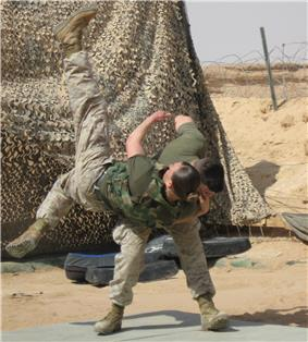 color photo of a Marine tossing another Marine over his shoulder onto a mat.