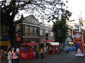 Road shown with a few shops housed in building constructed by the British.