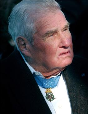 Head of an older white man with gray hair wearing a dark suit coat over a white shirt. A star-shaped medal hangs from a light-blue ribbon around his neck.