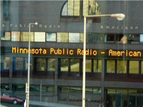 Four stories, with mirror-windows. Electric sign above second floor says MINNESOTA PUBLIC RADIO - AMERICAN.