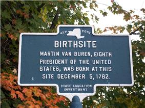 A bronze marker with a map of the State of New York at the top, under which is the word Birth site and other text