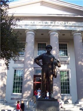 A large bronze statue of MacArthur stands on a pedestal before a large white building with columns. An inscription on the building reads: