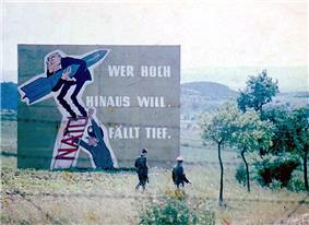 Two armed East German soldiers, seen through a barbed-wire fence, walking from right to left through a grassy hilly landscape towards a clump of young trees. Behind them is a very large propaganda sign showing a caricature of West German Chancellor Konrad Adenauer clutching a missile while standing on a ladder being propped up by a military officer. The rungs of the ladder are made from the acronym