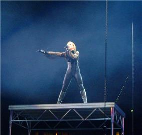 A blond woman stands on a steel tabletop. She wears a tight, body-hugging dress, accompanied by boots and gloves. She sings to a microphone in her left hand and her right hand is stretched out. The table is held by steel cables.
