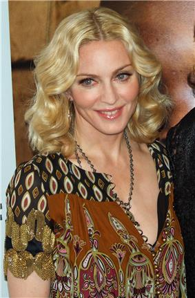 A blonde Caucasian female in a calico blouse and a silver chain smiles while looking to the left and slightly downward in front of a flesh-toned backdrop.