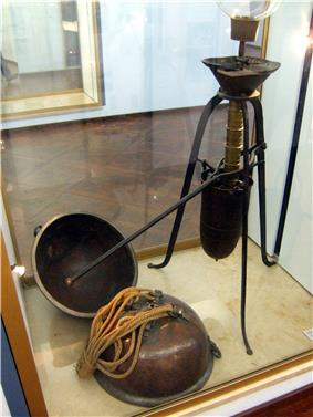 A glass display case holds a mechanical device with a lever arm, plus two metal hemispheres attached to draw ropes