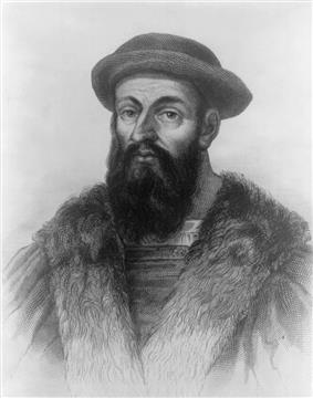 Head and shoulders of a heavily-bearded man wearing a cloak and a soft hat