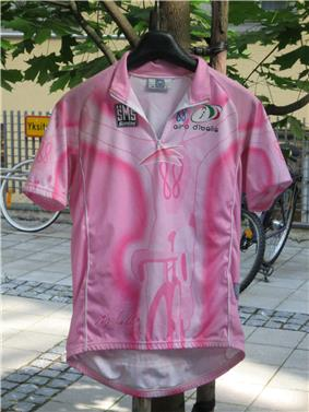 A pink jersey hung on coat-hanger, with bikes in the background