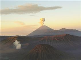 A brown volcano in the centre with white smoke emanating from its peak, a cloudy sky fading from blue at the top through yellow in the middle to red at the horizon, and brown mountains in the foreground.