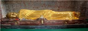 Gold colored statue of man reclining on his right side