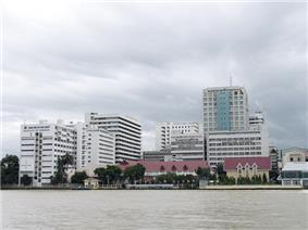 A large complex of buildings, most over ten storeys high, on the bank of a river; one bears a sign with the words