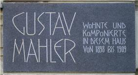 A dark plaque with white lettering in which the composer's name is shown in extra large characters on the left, the main message in smaller characters on the right