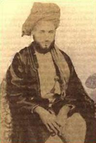 A black-and-white photograph of a man with a dark beard wearing a turban and robes, sitting on a patterned chair, and looking at the viewer