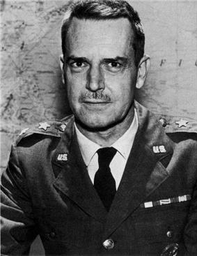 Man with dark hair and moustache in a dress uniform, consisting of a military suit and tie, sitting at a table, with two stars on each lapel indicating his rank, in front of a world map on a wall.
