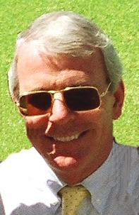 a smiling, clean-shaven middle-aged white man with grey hair, wearing sunglasses