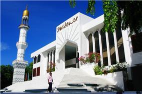 A white mosque under a blue sky.