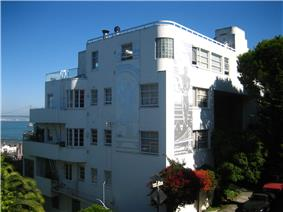 A white and silver building built with curved corners and streamlined features, stepped back along the slope of a hill.