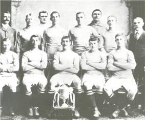 A group of thirteen men, eleven in association football attire typical of the early twentieth century and two in suits. A trophy sits in front of them
