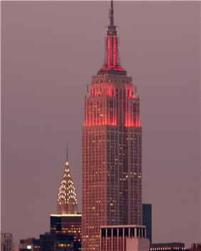 A tall, Art Deco building is shown in front of a cityscape at dusk. Lights aiming toward the top of the building glow red. The structure becomes slender as it grows taller, ending in a point at an antenna.