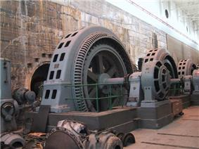 Interior of building showing three old fashioned vertical generators, like an upright wheel, each more than twice the height of a person.