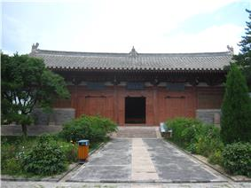 A Chinese temple building that is red. In front of it is a pathway and trees and flowers.