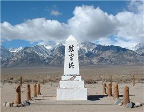 Photograph of a memorial at the Manzanar War Relocation Center. A low white obelisk with Japanese kenji characters and flower offerings stands against an expansive backdrop of the Owens Valley floor, snowy mountains, large clouds, and blue sky.